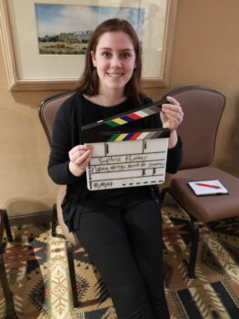 Portrait of a woman holding a film clapboard