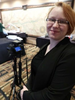 A woman standing next to a video camera