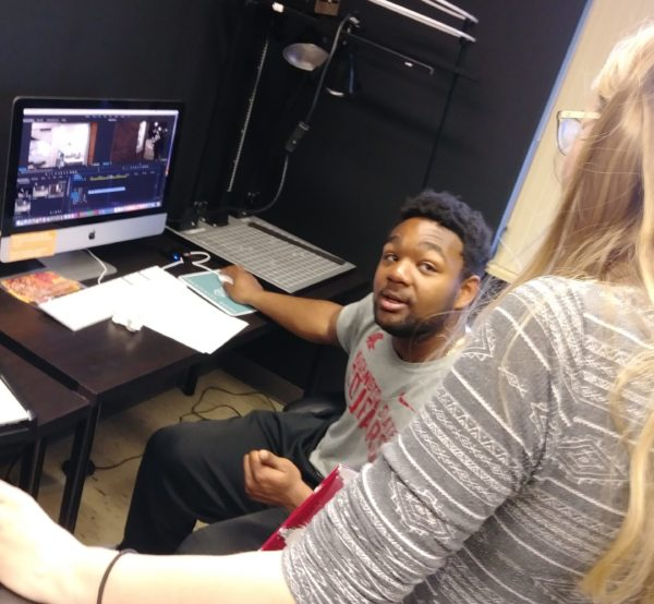 A young man confers with a young woman over a video editing project on a computer
