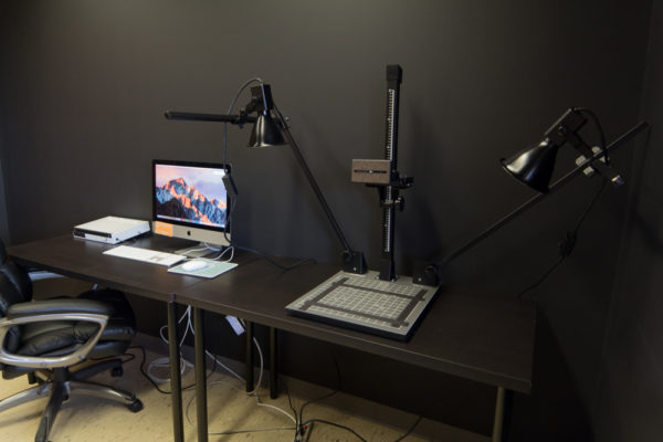 A dark room with an animation stand and a computer on a table