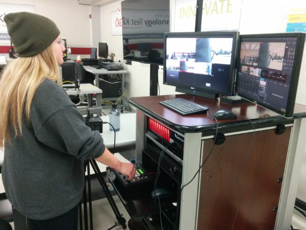 A young woman operates a digital video broadcaster