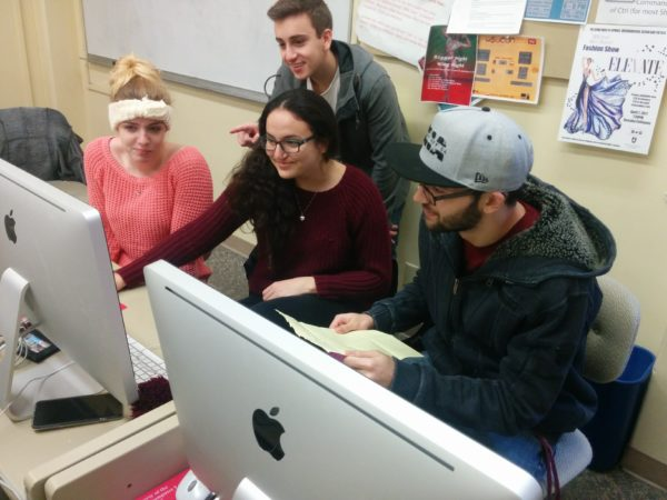 Two young women and two young men collaborate on a computer