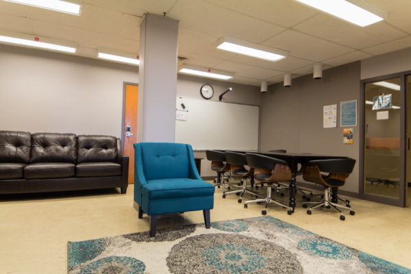 A grey room with several chairs, a conference table, and a couch