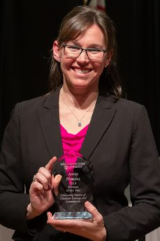 A middle age woman with glasses hold a glass award