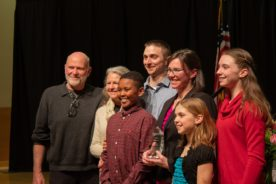 Six family members stand around Dr. Anna Plemons and her award