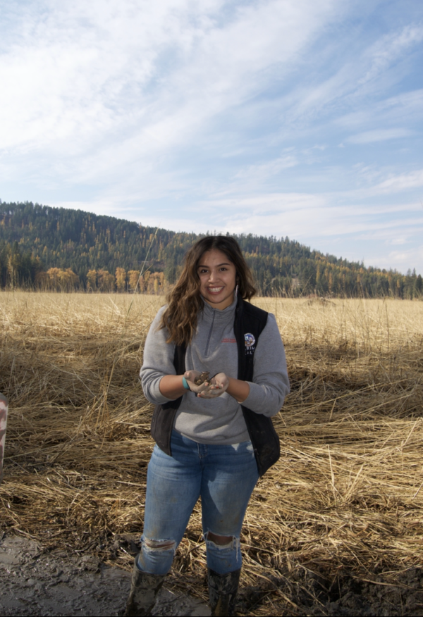 Kyra Antone stands in a field with a handful of dirt