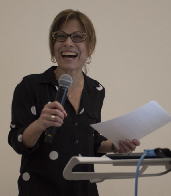 DTC Director Kim Christen is all smiles as she holds a mic at the 2019 DTC Awards