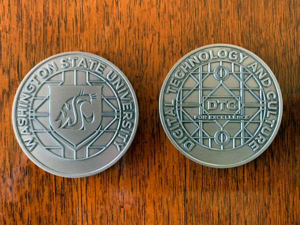"Two sides of a medallion coin. One says Washington State University and the other says Digital Technology and Culture ""For Excellence"""