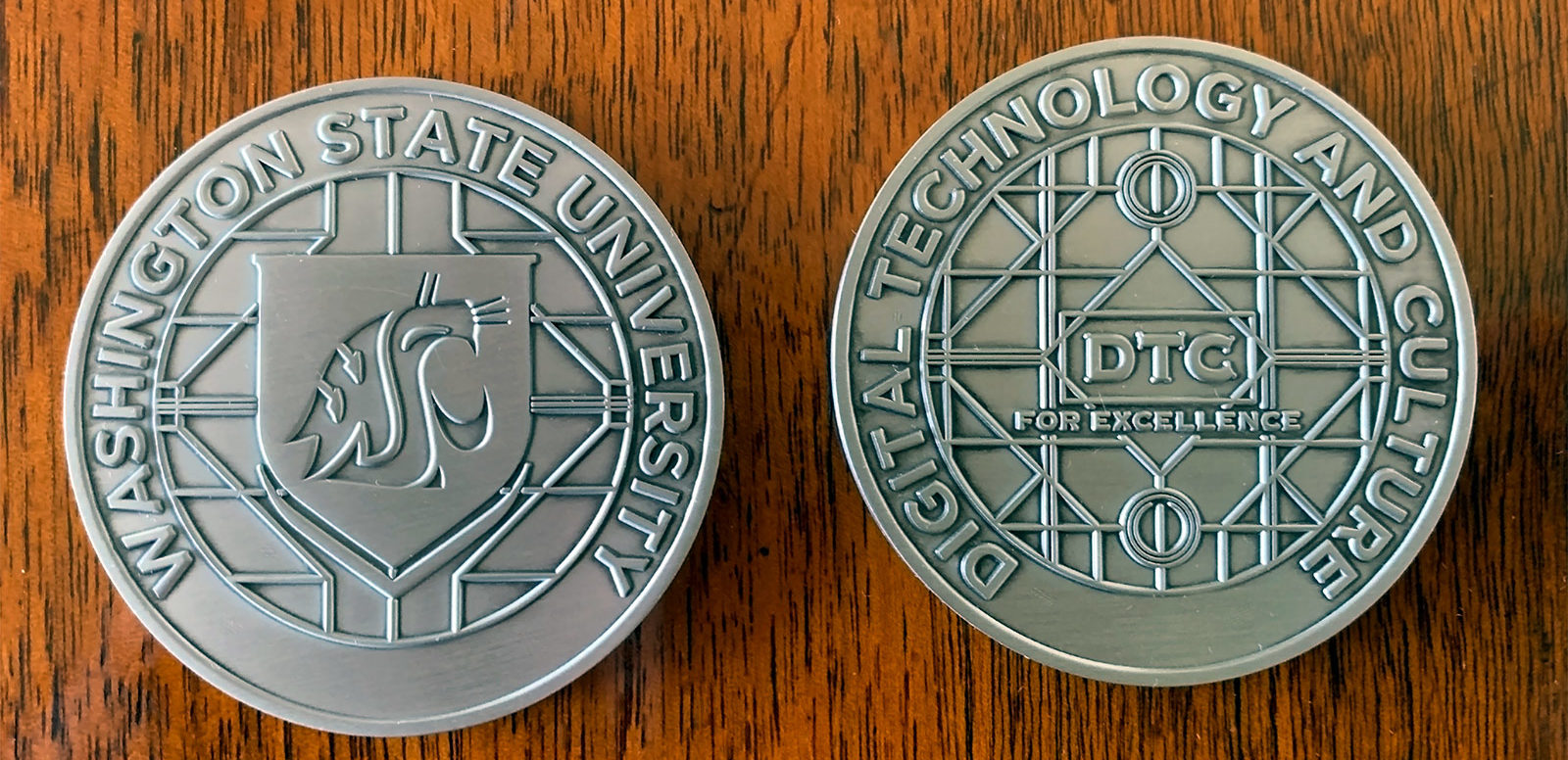 """Two sides of a medallion coin. One says Washington State University and the other says Digital Technology and Culture """"For Excellence"""""""