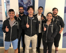 Kira Norman and five coworkers pose together in Airstrafe Interactive sweatshirts.