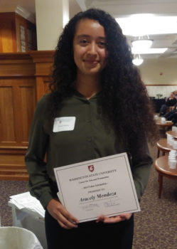 Aracely Mendoza holds her scholarship award certificate.