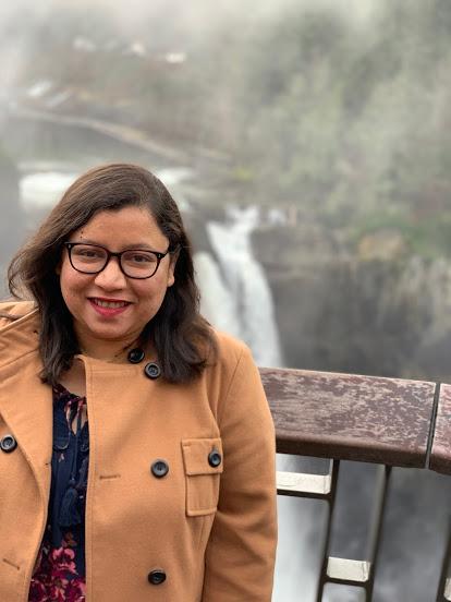 Nazua Idris standing in front of a waterfall