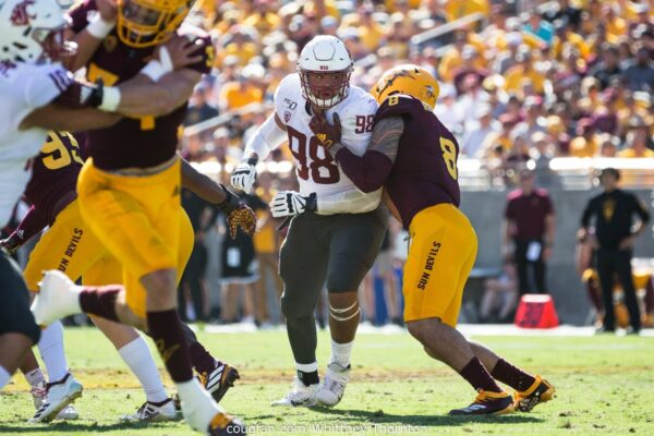 WSU Football Defensive Lineman Dallas Hobbs blocks an opposing player on the field