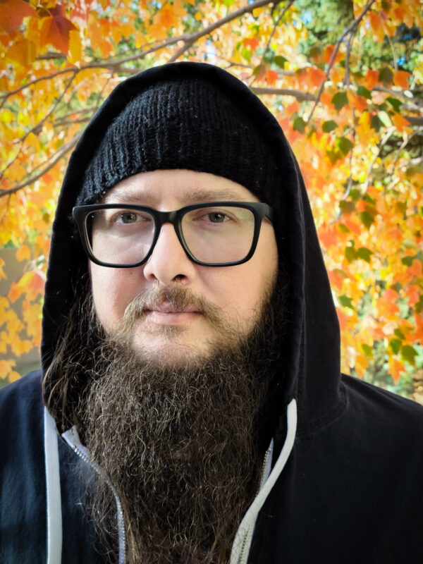 A man with dark rimmed glasses and a black hoodie
