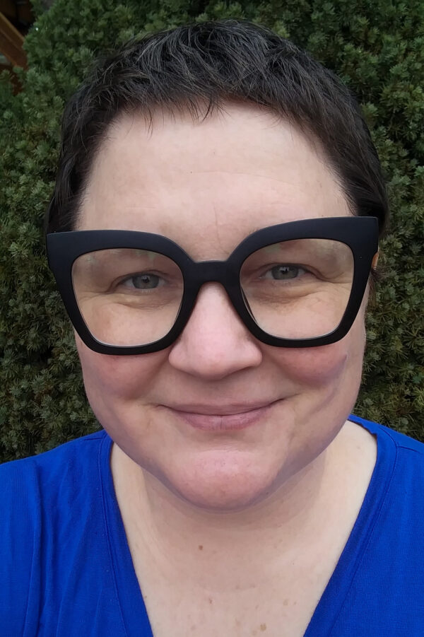 A woman with thick black glasses and short brown hair