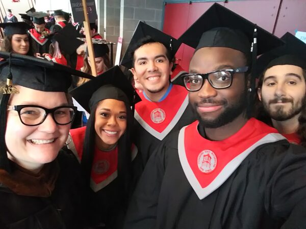 4 students in WSU graduation robes and one faculty member smile at the camera