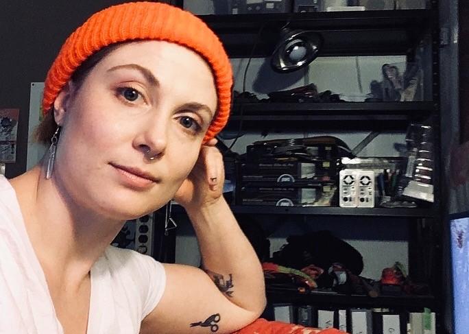 Jessica Earle poses in an orange beanie