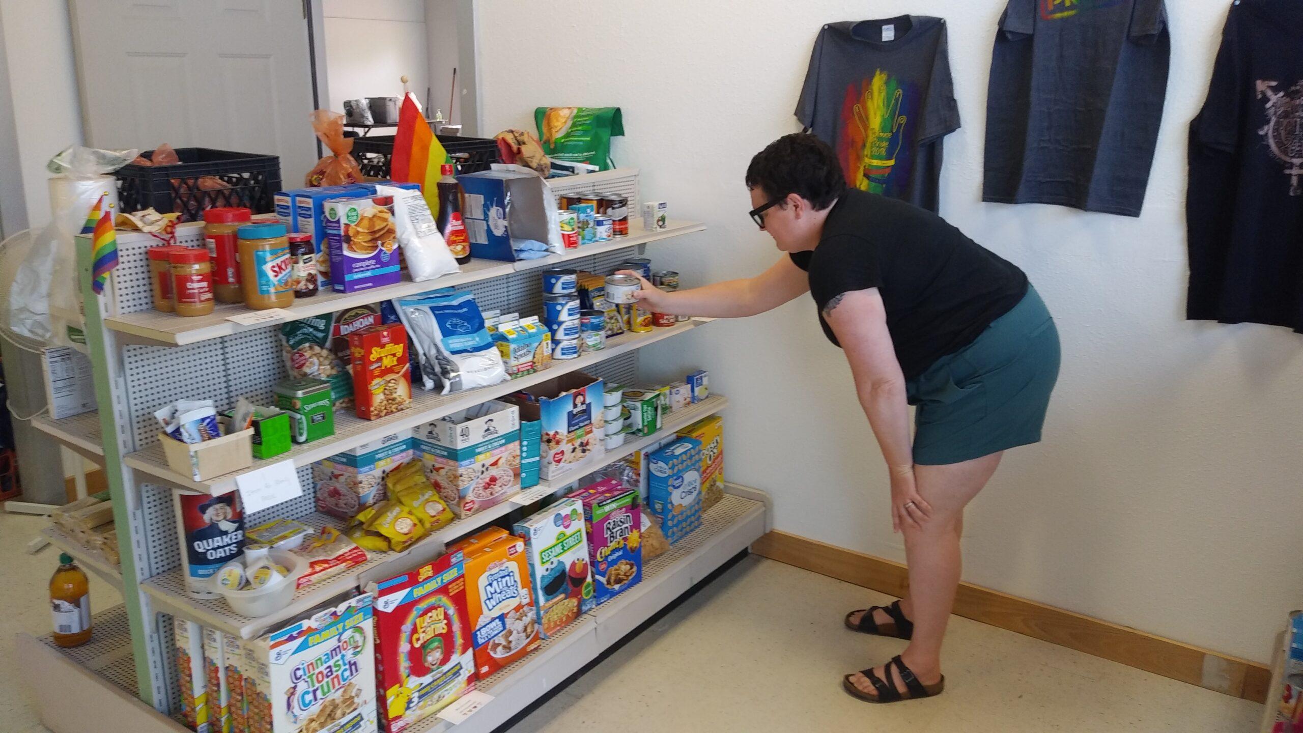 A woman stocks a shelf at a food bank