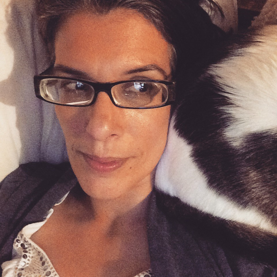 A woman wearing glasses looks at her cat