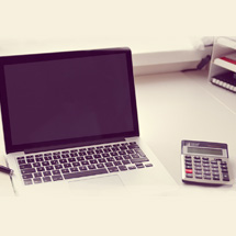 Image: Laptop, pens and calculator on desk.