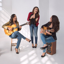 Image: Two women playing guitars and one woman singing