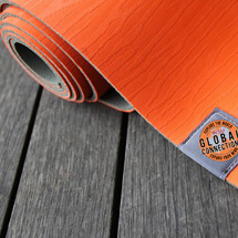 Image: Orange yoga mat partially unrolled on wooden floor with Global Connections logo.