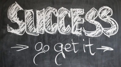 White chalk writing on blackboard: Success Go Get It.