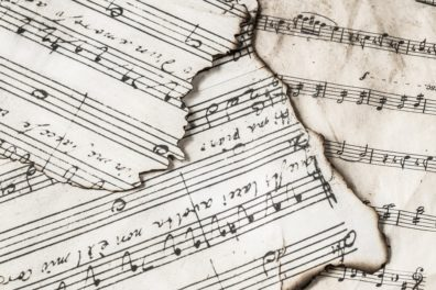 Photo: Overlapping torn scraps of sheet music.