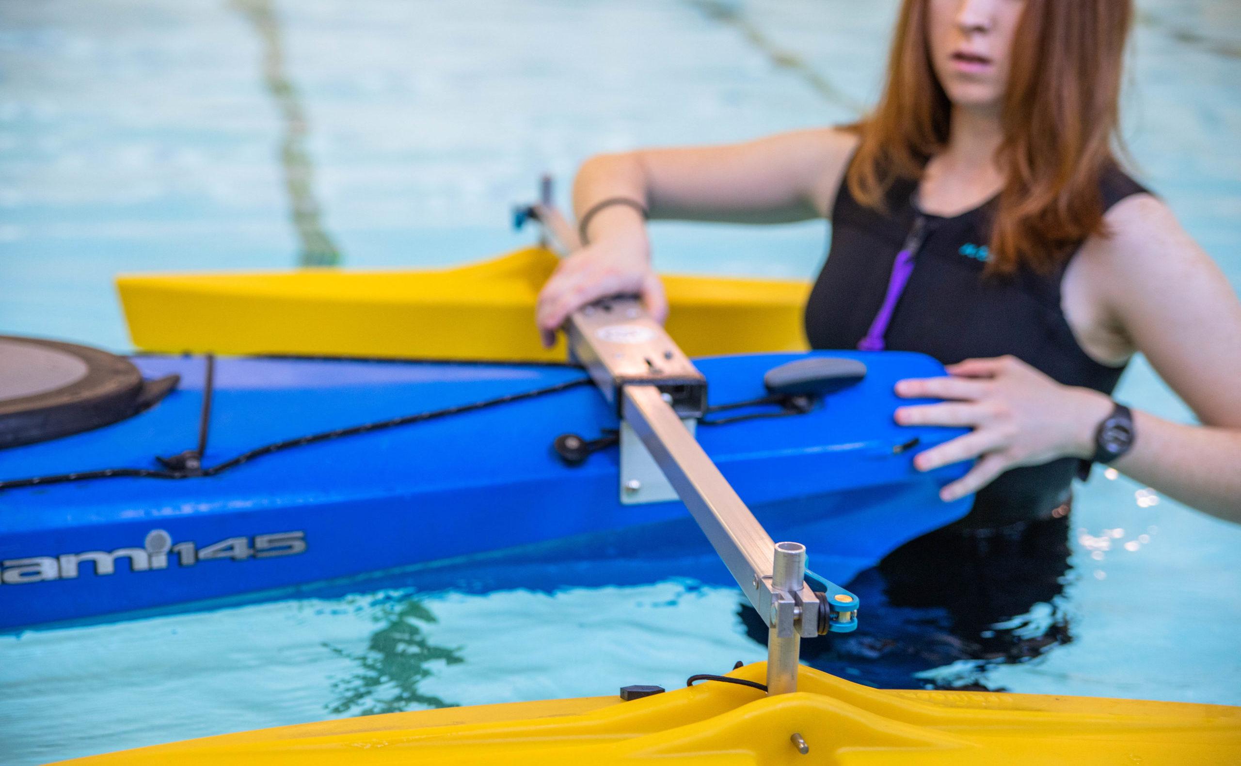 Photo: Woman holding kayak in pool