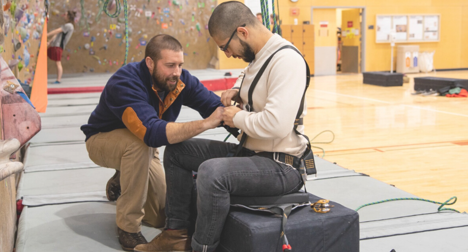 Photo: Man getting geared up to climb indoor climbing wall