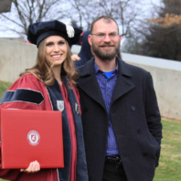 Jennifer Binczewski in her graduateion regalia with Prof. Jesse Spohnholz.