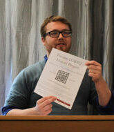 Brian Stack holds a document with a QR code.
