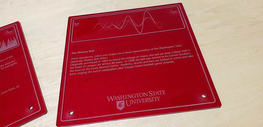 Photo: Wall plaque on The Victory Bell, showing a waveform and text: These waveforms, colors and shapes are a visual representation of the Washington State University Victory Bell chime. Originally purchased in 1892 to sound the change of classes, the bell sat atop College Hall in the heart of campus for almost 80 years. In 1998 the bell was moved to its current location, the lawn of the Lewis Alumni Centre. Students, alumni and fans are invited to come and take turns ringing the bell in celebration after cougar home football game victories.