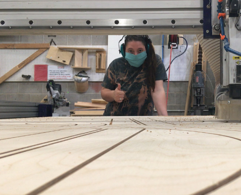 Photo: Student gives thumbs up behind CNC Milling and Cutting machine.