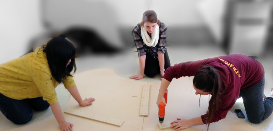 Photo: Three students work at fabricating early table prototype.