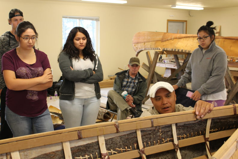 Dr. Brigman holds frame of canoe while students watch in background.