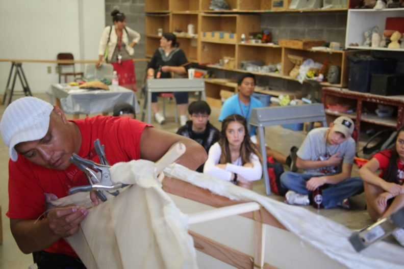 Dr. Brigman sews a canvas skin to a canoe frame while youth watch in the background.