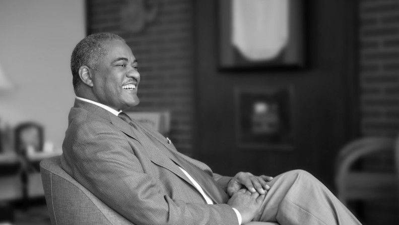 A black and white photograph of Elson Floyd sitting in a chair smiling