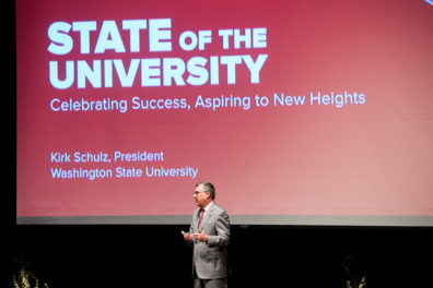 President Schulz stands in front of a presentation power point while addressing the audience