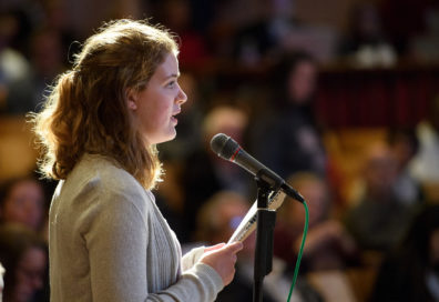 A student speaks to an audience over a microphone while holding questions in her hand.