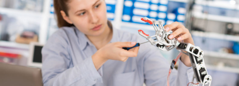 schoolgirl adjusts robot arm model