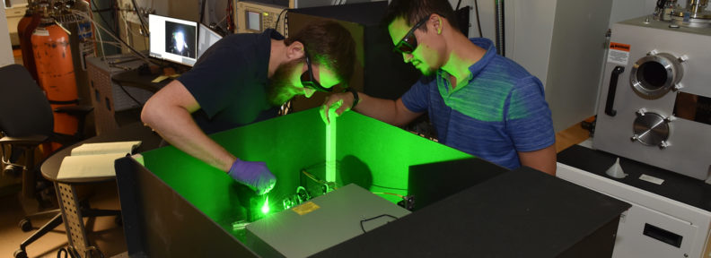 Researchers work with green laser in the lab