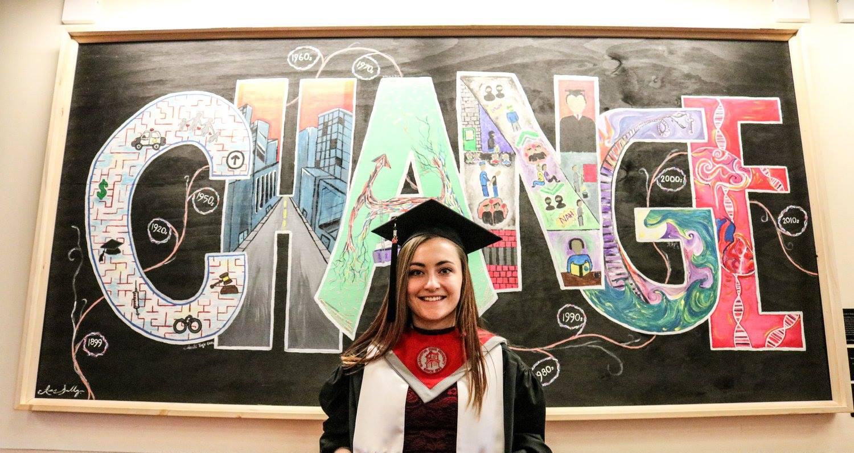 Mikala Ewert in graduation cap & gown in front of CHANGE mural.