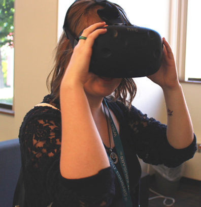 A student peers into a electronic landscape through a virtual reality headset.