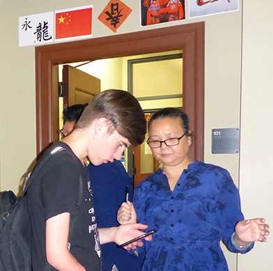 Trenton Kirchberg and Hong Wei Wang discuss the meaning of Chinese characters in an image on his phone.