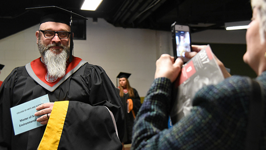 WSU graduate in his cap and gown getting photo taken