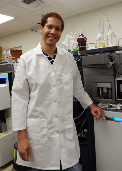Korey Brownstein in front of a liquid chromatography-mass spectrometry machine