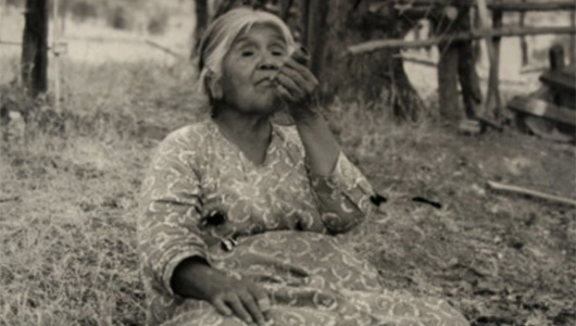 A 1945 picture of a Yokuts Native American woman smoking a pipe