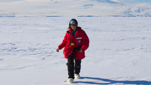 Researcher in red coat in snow field