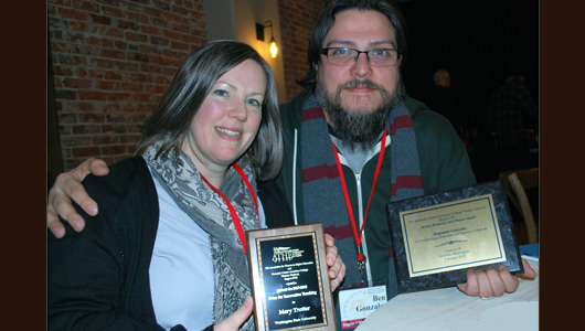 Two faculty holding award plaques